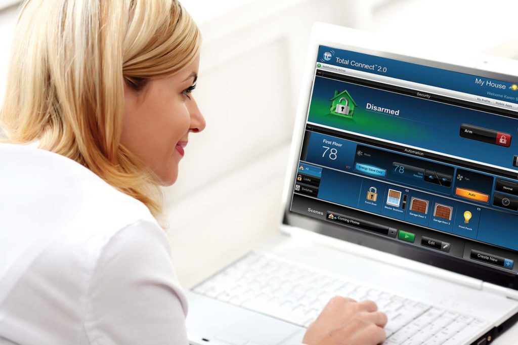 Smiling woman accessing her home automation security system on a laptop.