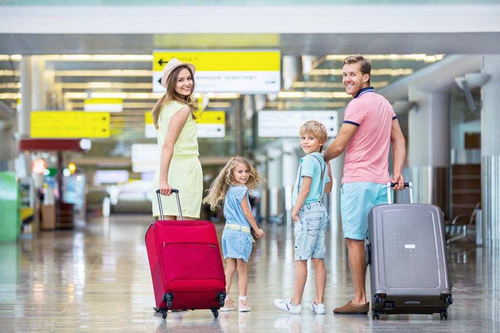 Smiling family with suitcases walking in an airport