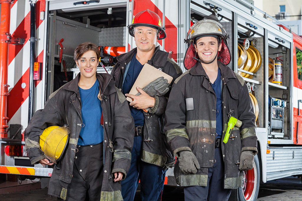 Three firefighters in firefighting equipment standing behind a firetruck.