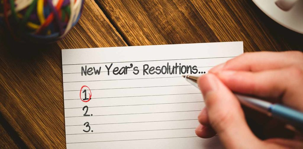 Hand with a pen writing New Year's resolutions on a notecard
