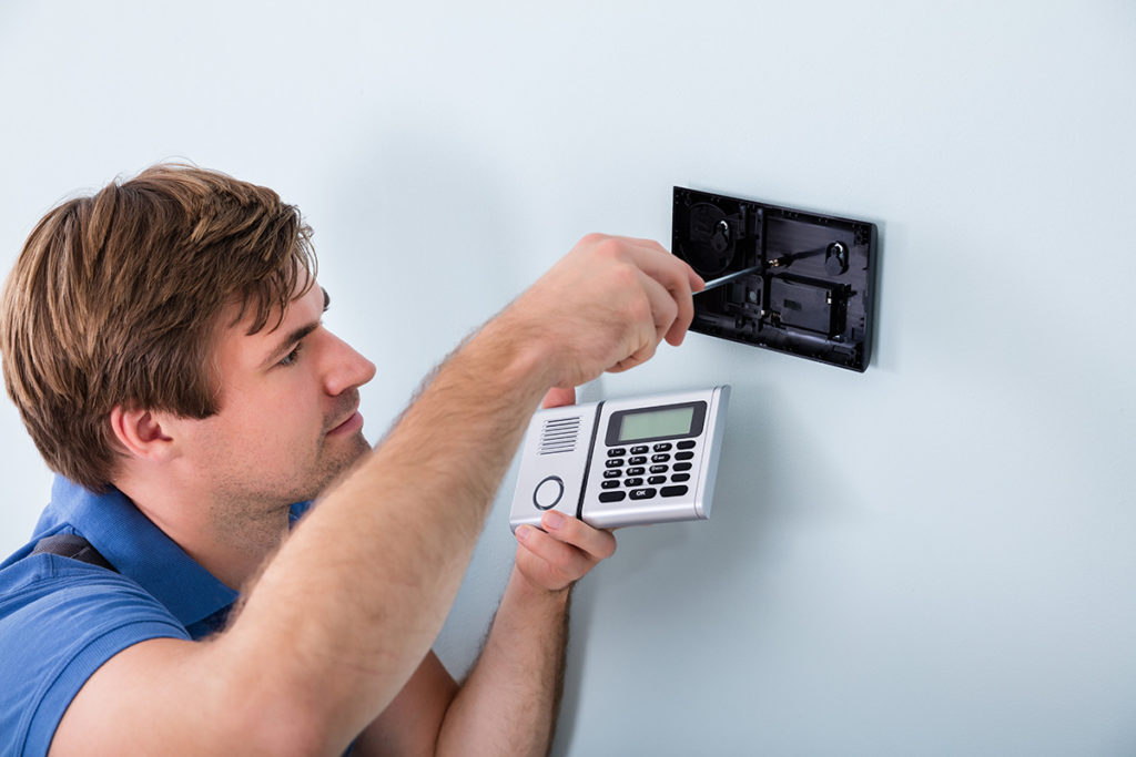Man installing a DIY home security system.